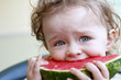 Small toddler eating melon
