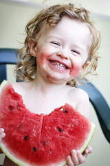 Little girl laughing and eating melon