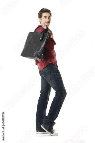 young Casual man walking holding a bag