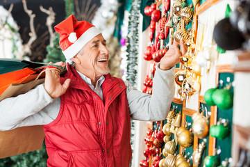 Man Buying Christmas Ornaments At Store