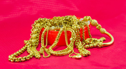 gold necklace red background
