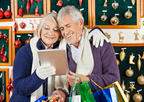 Happy Couple Using Digital Tablet At Christmas Store