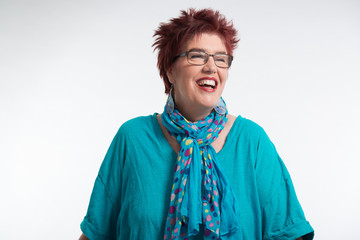 Happy smiling middle aged woman with red short hair and glasses.