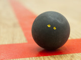 Black squash ball on t-line