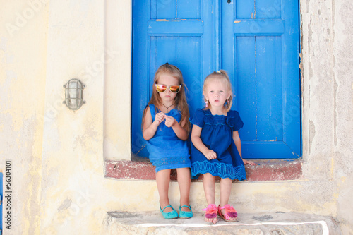 Little cute sisters sitting near old blue door in Greek village