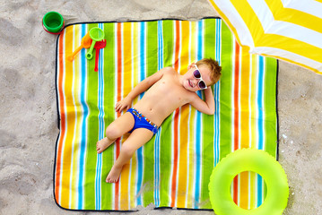 happy kid sunbathing on colorful beach
