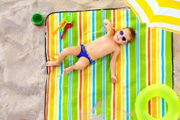 happy kid sunbathing on colorful beach