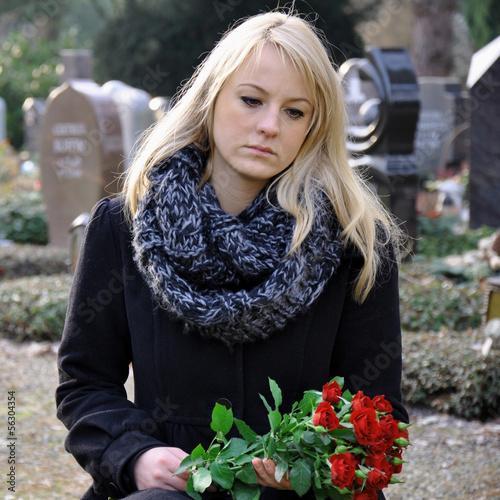 Leinwanddruck Bild Frau trauert auf Friedhof