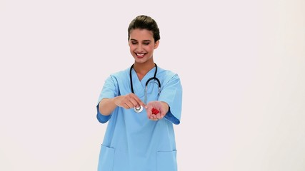 Content beautiful nurse showing red pills in her hand