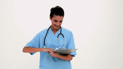 Cheerful beautiful nurse filling a report
