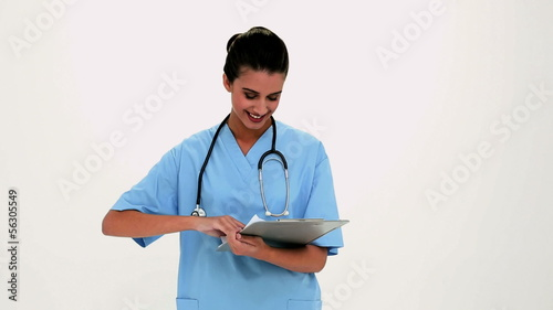 Cheerful beautiful nurse filling a report