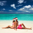 Couple in santa's hat on a beach at Maldives