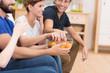 freunde sitzen zusammen und essen chips