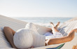 Peaceful woman in sunhat relaxing on hammock - 56308369