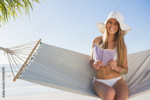 Smiling blonde wearing sunhat sitting on hammock holding book