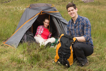 Smiling man packing backpack while girlfriend sits in tent