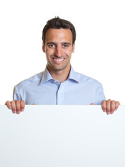Smiling latin man with a signboard for advertising