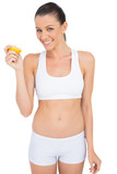 Smiling woman in sportswear holding slice of orange looking at c