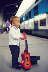 Little boy on a railway station with a guitar