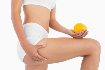 Female body holding orange and squeezing her thigh