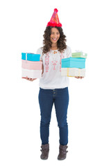Cheerful casual brunette wearing party hat holding presents