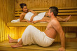 Calm couple relaxing in a sauna and chatting