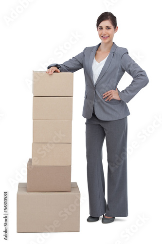 Serious businesswoman with cardboard boxes on her side