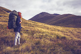 Woman with backpack about to climb mountain