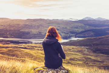Woman looking at the sunset over mountains