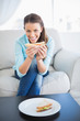 Happy woman sitting on sofa showing sandwich at camera
