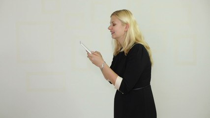 Happy businesswoman texting message on digital tablet
