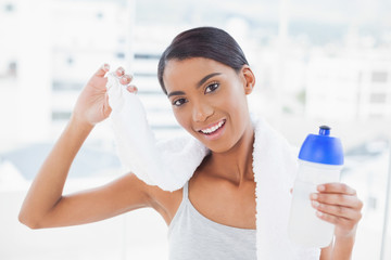 Smiling sporty model holding flask and sport towel