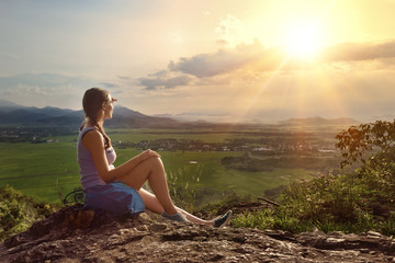Girl sits on edge of cliff looking at sun and mountains