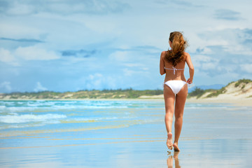 A woman running along the beach in a white bikini