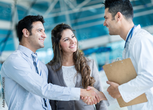 Family doctor handshaking a couple