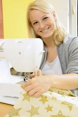 Frau beim Nähen mit Nähmaschine