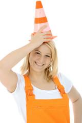 Weiblicher Bauarbeiter trägt Pylon als Hut