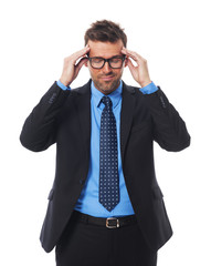 Businessman wearing glasses with awful headache