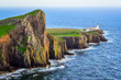 View of Neist Point lighthouse and rocky ocean coastline, Scotla