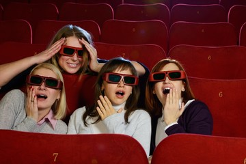 Group of excited young girls watching movie