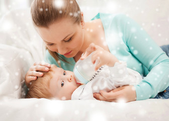 mother and adorable baby with feeding-bottle