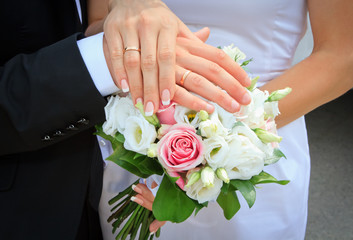 Hands and rings on wedding bouquet