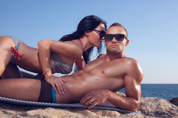 passionate couple in sunglasses lying on the sea