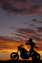 silhouette of woman motorcycle sit backwards hand