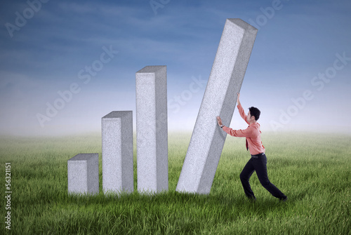 Young businessman pushing a bar chart outdoor