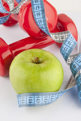 Apple, measurement tape and dumbbell 8