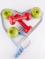 Apple, measurement tape and dumbbell