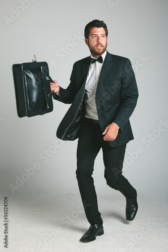 Stylish young man with black suit and briefcase.