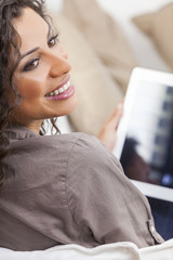 Hispanic Woman Laughing Using Tablet Computer
