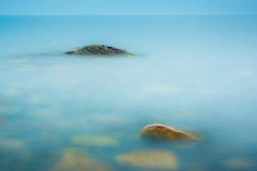 Three rocks in the still water